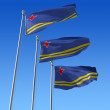 Three flags of Aruba against blue sky. - Stock Photo