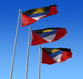 Three flags of Antigua and Barbuda against blue sky. — Stock Photo