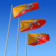 Royalty-Free Stock Photo: Three flags of Bhutan against blue sky.
