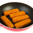 Red frying pan with fish sticks — Stock Photo