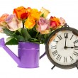 Roses in watering can with vintage clock — Stock Photo