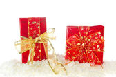 Red and golden Christmas presents in snow — Stock Photo