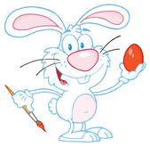 Conejo de pascua pintando un huevo blanco — Foto de Stock