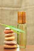 Essential spa oil and heating stones — Stock Photo