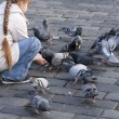 Stock Photo: Kid feeding pigeons