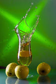 Green apples and glass with juice — Stock Photo