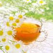 Cup of chamomile tea over white background — Stock Photo