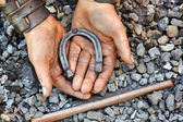 Detail of dirty hands holding horseshoe - blacksmith — Stock Photo