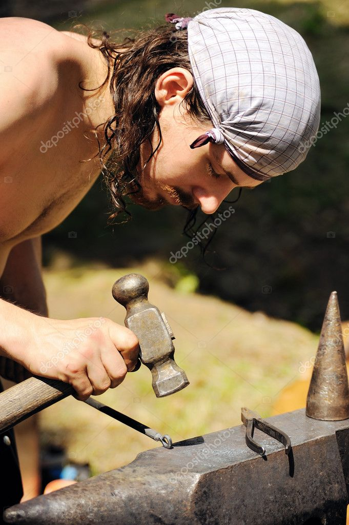 Young blacksmith hammering hot iron on anvil — Stock Photo #7606303