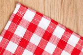 Kostkovaný ubrus na dřevěný stůl — Stock fotografie