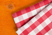 Checkered napkin on wooden table — Stock Photo