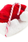 Stripy candy cane and xmas hat — Stock Photo