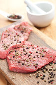 Raw beef steak with pepper — Stock Photo