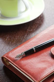 Pen on diary and coffee mug — Stock Photo