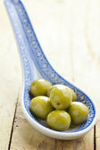 The green olives in ceramic spoon — Stock Photo