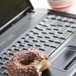 Break in the  office . doughnut on laptop keyboard — Stock Photo