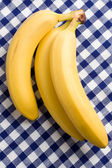 Yellow bananas on checkered tablecloth — Stock Photo