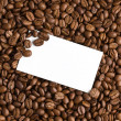 White card on coffee beans background — Stok fotoğraf