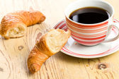 Breaking croissant with coffee — Stock Photo