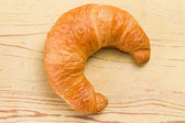 Fresh croissant on wooden table — Stock Photo