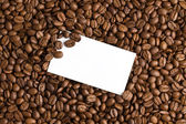 White card on coffee beans background — Stock Photo