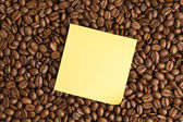 Yellow note paper on coffee beans background — Stock Photo