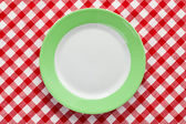 Green plate on checkered tablecloth — Stock Photo