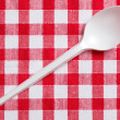 Plastic spoon on checkered tablecloth — Photo