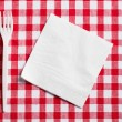 Plastic cutlery on checkered tablecloth — Stock Photo