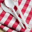 Plastic cutlery on checkered tablecloth - Stock Photo
