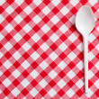 Plastic spoon on checkered tablecloth - Stock Photo