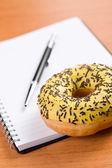 Sweet doughnut and spiral notebook — Stock Photo