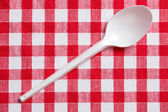 Plastic spoon on checkered tablecloth — Stock Photo