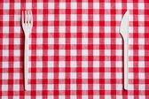 Plastové příbory na kostkovaný ubrus — Stock fotografie