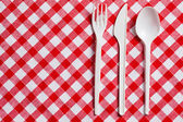 Plastic cutlery on checkered tablecloth — 图库照片