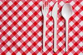 方格桌布上的塑料餐具 — 图库照片