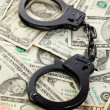 Handcuffs on dollars — Stock Photo