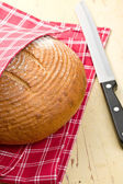 Round bread on kitchen table — Stock Photo