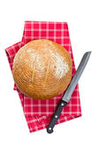 Round bread with knife on checkered napkin — Stock Photo