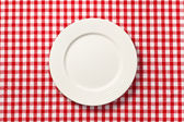 White plate on checkered tablecloth — Stock Photo