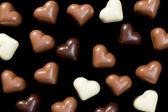 Chocolate hearts on black — Stock Photo