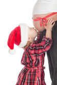 Little girl kissing christmas gift - pregnant mother — Stock Photo