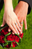 Hands with rings on wedding bouquet — Stock Photo