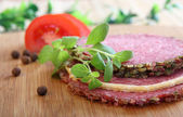 Salami slices and tomato with Marjoram herb — Stock Photo