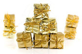 Gold wrapped parcels on a white background — Stock Photo