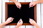 Blackboard with many hands with chalk — Stock Photo