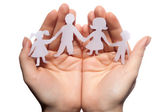 Paper chain family protected in cupped hands — Stock Photo