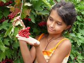 The girl standing beside a red viburnum — Stock Photo
