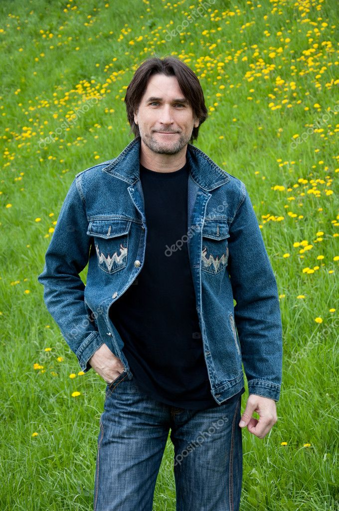 The dark-haired man in jeans on a meadow — Stock Photo #6931198