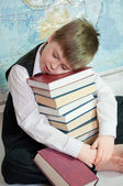 Tired schoolboy with a pile of books on a map of the world — Stock Photo